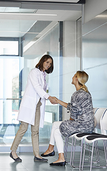 Young woman shaking hands with female doctor in waiting room. Female patient is visiting healthcare worker. They are in hospital.